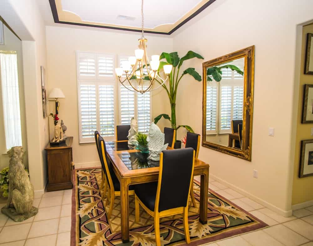 Tropical dining room with black cushioned chairs and a wooden dining table topped with a potted plant and fish decors. It includes a brass chandelier and framed mirror along with an eye-catching rug that lays on the tiled flooring.