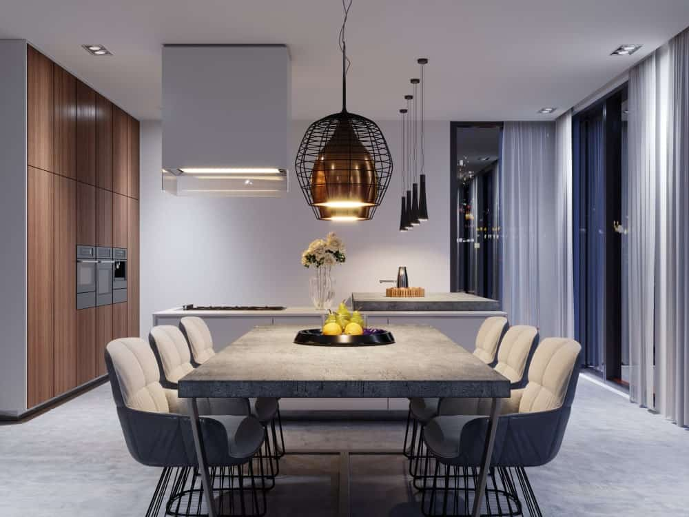 An open dining area illuminated by a pair of caged pendant lights that hung over the wooden dining table paired with gray upholstered chairs on carpet flooring.