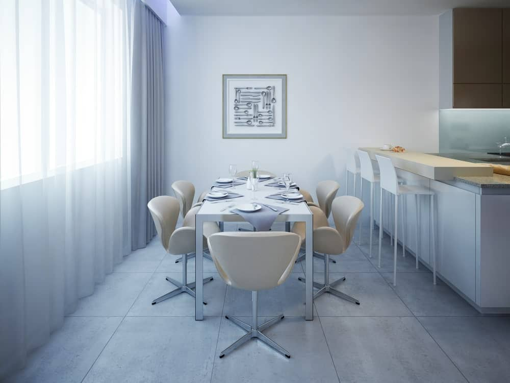 A dining area next to the bar featuring a sleek dining table and gorgeous chairs against the glazed window covered with sheer curtains. It is accented with utensil art piece mounted on the white wall.