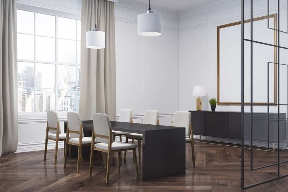 Modern dining room with herringbone wood flooring and white framed windows covered in gray draperies. It includes a dining set for six and a black console table paired with a large mirror that's mounted on the white wainscoted wall.