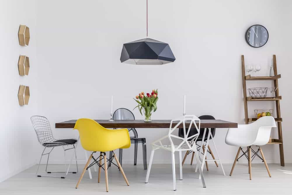 Industrial dining room illuminated by a geometric pendant light that hung over the dark wood dining table surrounded with mismatched chairs. It has hexagon shelves and a wooden shelving unit resembling like a ladder.