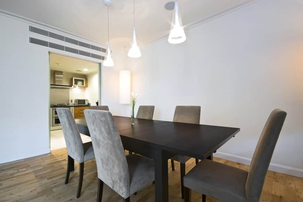 Minimalist dining room with gray velvet chairs and dark wood dining table topped with a glass flower vase. It is lighted by cone pendant lights and a cylindrical sconce mounted on the corner wall.