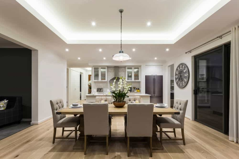 Well-lit dining room decorated with a round wall clock and a dome pendant light that hung over the wooden dining table accompanied by beige tufted chairs on wood plank flooring.