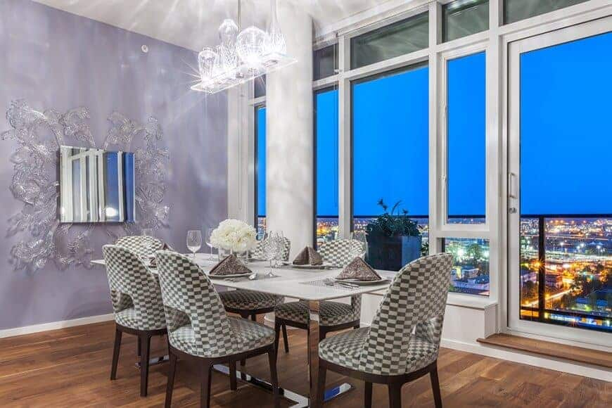 Fabulous dining room decorated with a gorgeous mirror and a crystal pendant that hung over the sleek dining table paired with checkered round back chairs. It has wide plank flooring and full height windows framing an amazing city view.