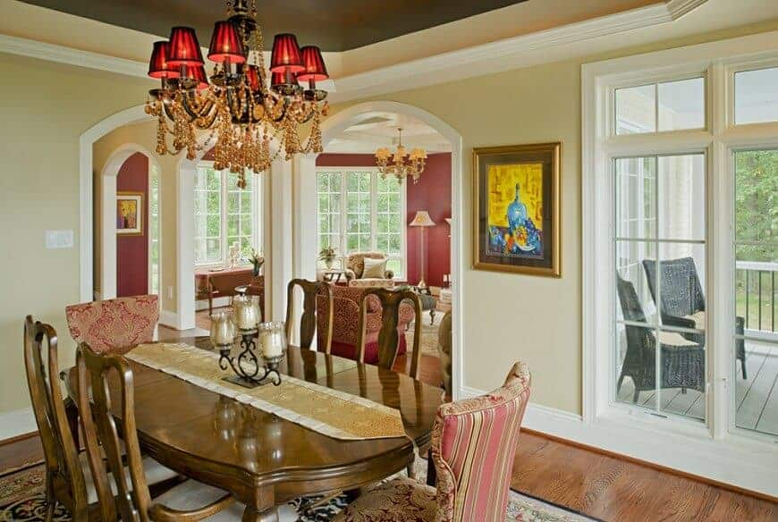A classy runner lays on the wooden dining table in this beige dining room with a glam chandelier and cushioned chairs that sit on a floral area rug.