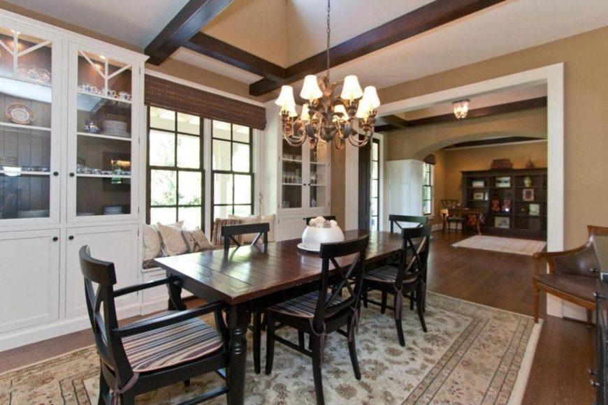 The classic dining room boasts striped cushioned chairs and a wood plank dining table lighted by a traditional chandelier. It sits on a floral rug and across the window seat nook flanked by glass front cabinets.