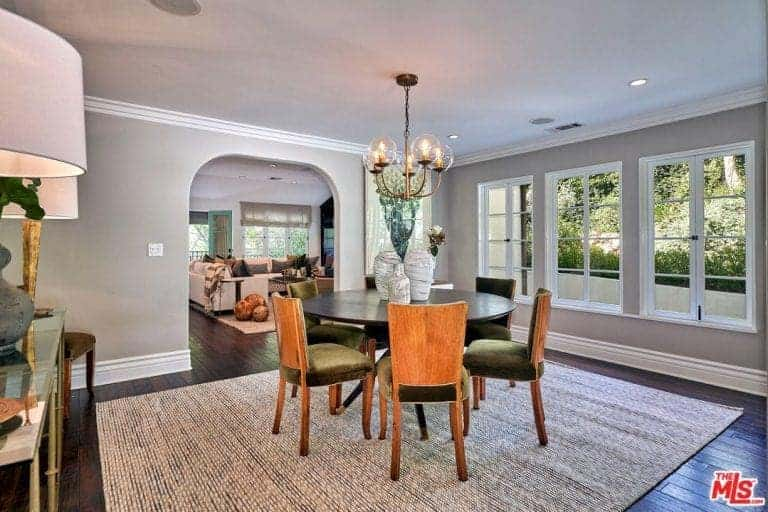 This dining room showcases round dining set on a striking area rug illuminated by glass globe chandelier. It has white framed windows and an open archway leading out to the living area.