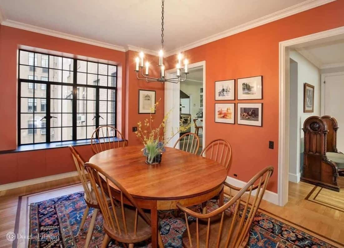 Red dining room features gallery wall and a candle chandelier that hung over the wooden dining set on a printed area rug. It has hardwood flooring and glazed windows framed in black aluminum.