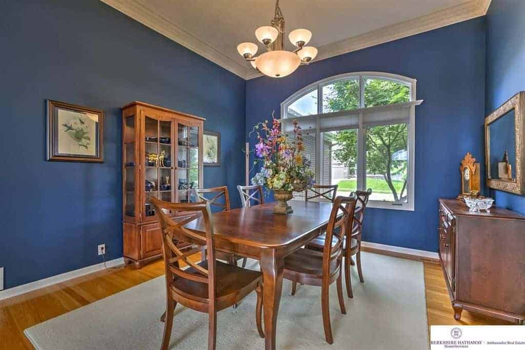 Blue dining room with a wooden dining set for six situated in between the console table and china cabinet displaying deep blue dinnerware.