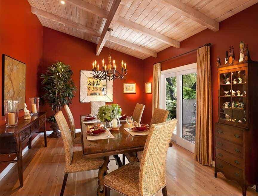 A potted plant in the corner creates a tropical feel in this red dining room furnished with a display cabinet, wicker dining set and a console table accented with a lovely artwork.