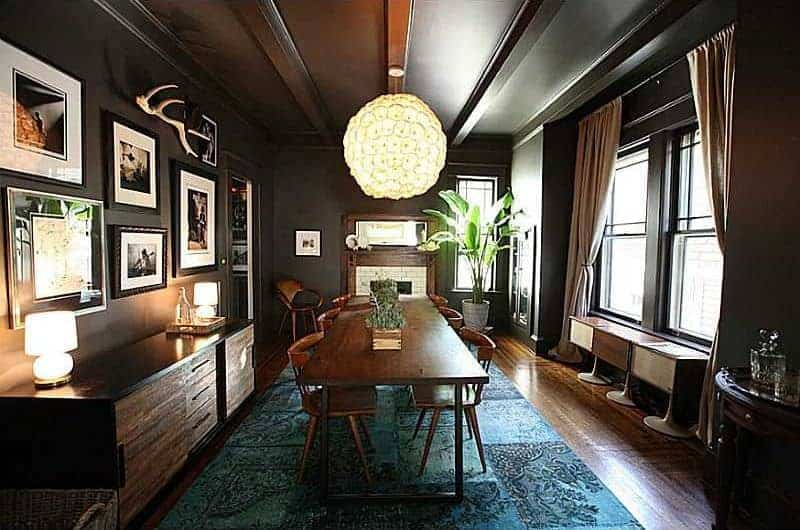 Black dining room designed with a spherical chandelier and photo gallery mounted above the console table. It has a wooden dining table and round back chairs that sit on a blue area rug.