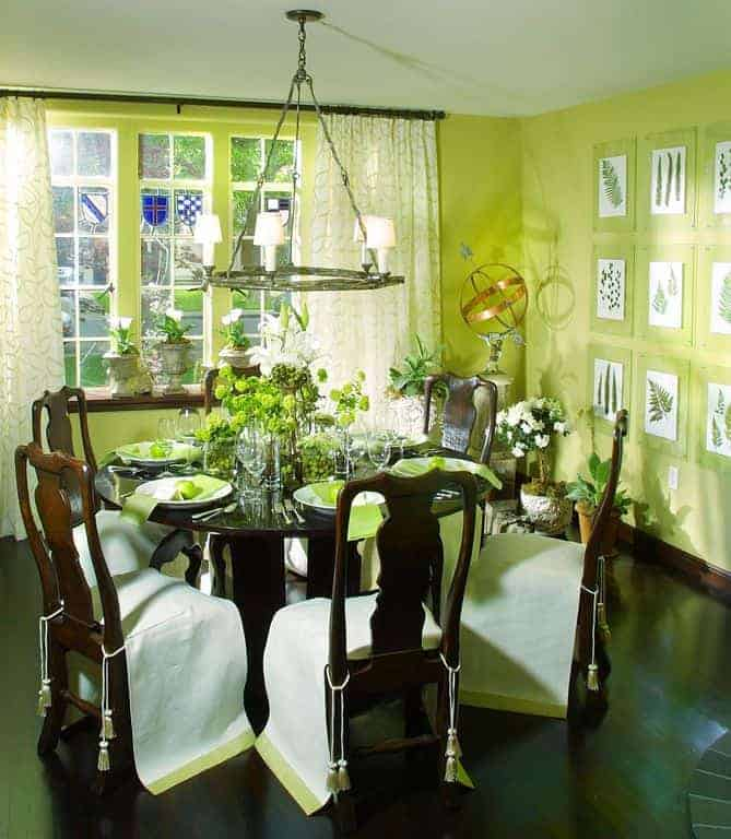 Green dining room decorated with potted plants and botanical gallery mounted across the wooden chairs and glass top dining table lighted by a round chandelier.