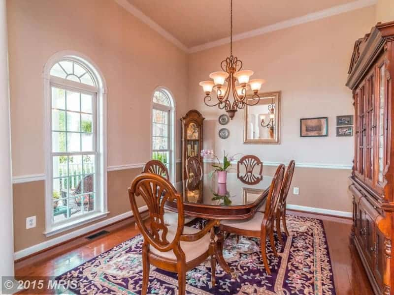 Charming dining room showcases arched windows and rich wide plank flooring complementing with the display cabinet and wooden dining set on a floral area rug.