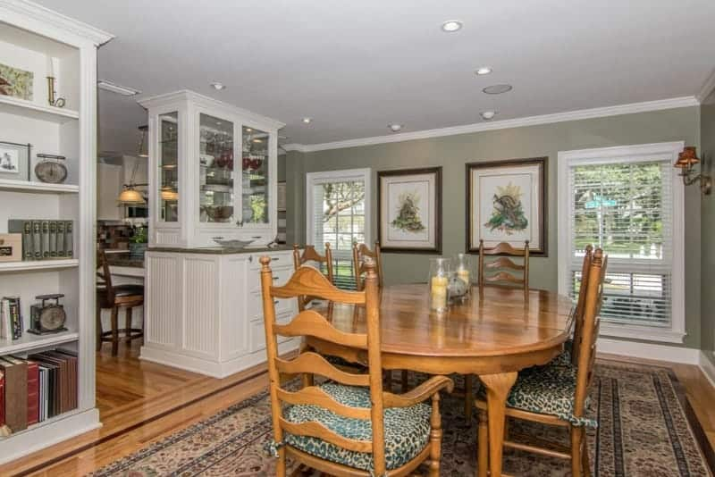 A wooden dining set sits on a bordered area rug in this dining room with a white bookshelf and display cabinet serving as a divider from the kitchen area.