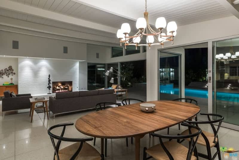 A dining space behind the living area boasting round back chairs and an oval dining table illuminated by a copper chandelier that hung from the beamed ceiling.