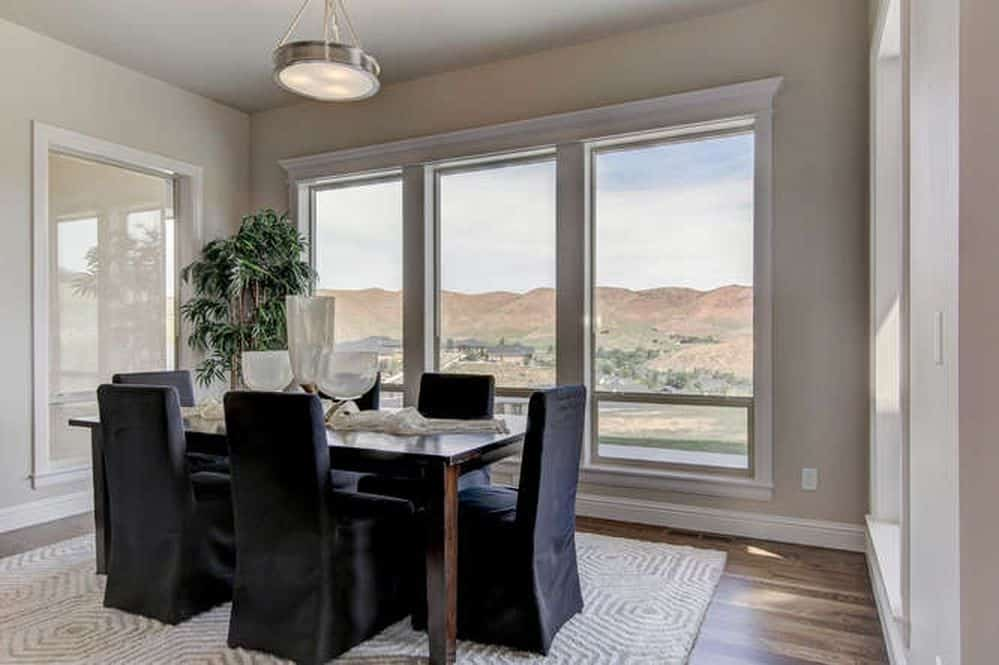 A patterned textured rug lays on the natural hardwood flooring in this bright dining room with a six-seater dining table and three-panel window overlooking a magnificent mountain view.