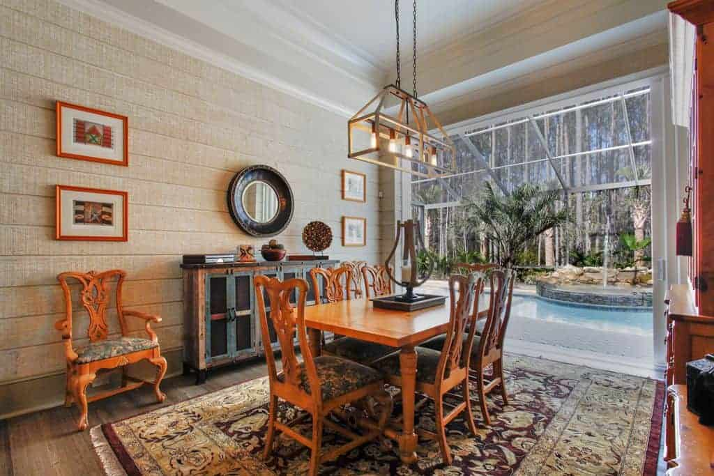 Fresh dining room designed with framed artworks and a round mirror that hangs above the console table placed against the shiplap wall. It has a rustic chandelier and a wooden dining set that sits on a floral rug.