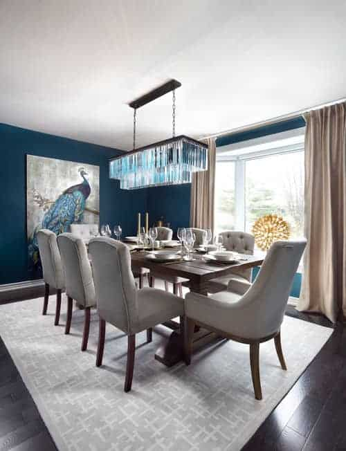 Sophisticated dining room decorated with a stunning peacock canvas and fancy crystal chandelier that hung over the wood plank dining table surrounded by beige tufted chairs.