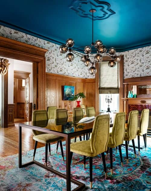 A contemporary chandelier hangs over the rectangular dining table in this gorgeous dining room clad in floral wallpaper and wooden wainscoting. It has a beautiful blue ceiling and hardwood flooring topped by a vintage rug.