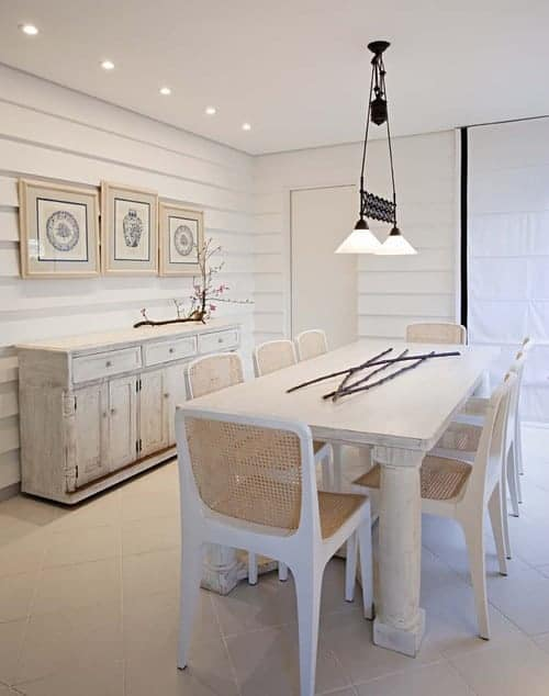 White dining room showcases recessed ceiling lights and shiplap walls mounted with framed art pieces. It includes a distressed buffet table and a chic dining set lighted by glass dome pendants.