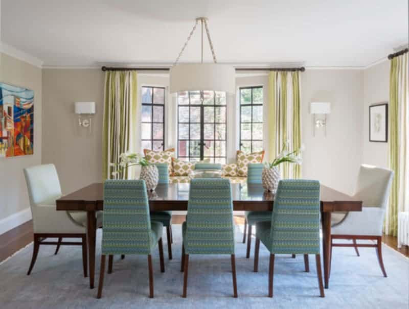 This dining room showcases a drum pendant light and a dark wood dining table paired with white and charming blue chairs. It sits across the window seat nook completed with green patterned cushion and matching pillows.