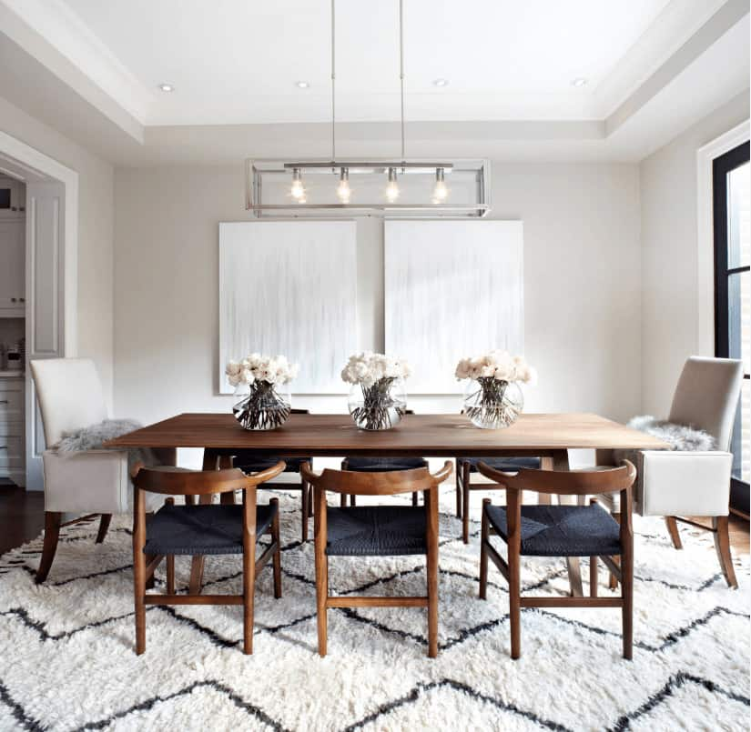 This dining room boasts minimalist wall arts and a wooden dining table accompanied by white leather and black round back chairs over a shaggy area rug. It is illuminated by a linear chandelier and recessed lights mounted on the tray ceiling.