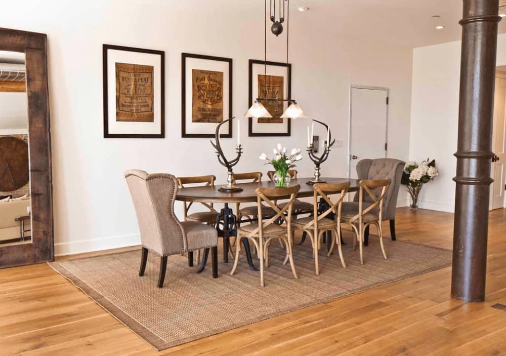 This dining room boasts an oval dining table topped with antler candle holders and accompanied by wooden and tufted wingback chairs on a jute rug. It is lined with a pipe column that complements the large framed mirror.