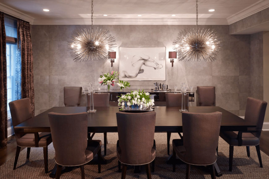 A white wall art hangs above the console table in this dining room illuminated by wall sconces and sputnik chandeliers that hung over the dark wood dining table surrounded by brown upholstered chairs.