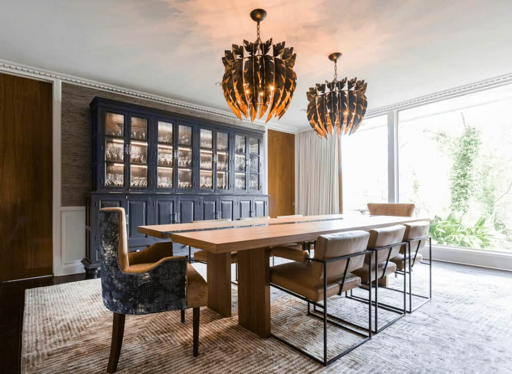 Marvelous dining room showcases a deep blue display cabinet and a stylish dining set for eight lighted by a pair of eccentric chandeliers. It has full height glazing and dark hardwood flooring topped by a textured rug.