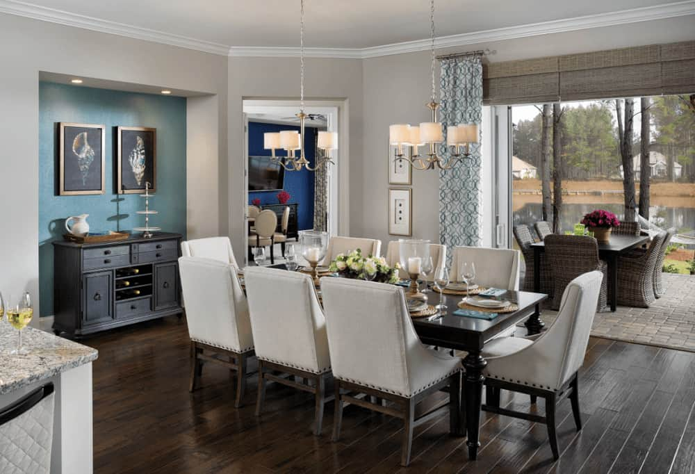 Transitional dining room offers a classy dining set for eight and a dark wood buffet table that's accented with framed art pieces mounted on the inset wall.