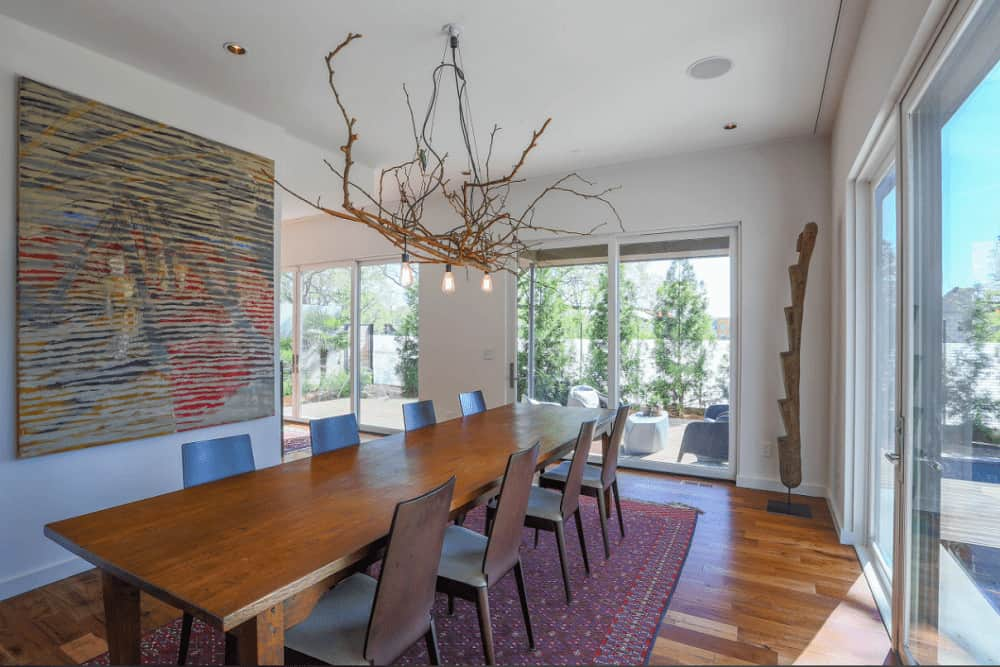 Bulb pendant lights are strangled on twig branches in this dining room with gorgeous artwork and a long dining set that complements the wood plank flooring topped by a plum patterned rug.