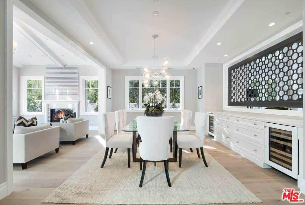 White dining area features wingback chairs and a glass top dining table illuminated by glass globe chandelier. It includes a jute area rug and built-in cabinet under a perforated panel.