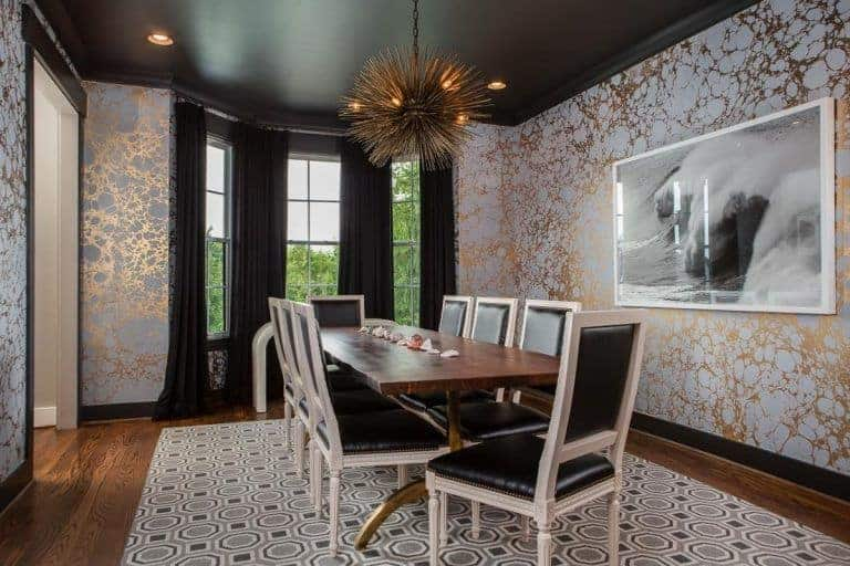 Clad in classy wallpaper, this dining room showcases a black and white wall art along with a sputnik chandelier that hung over the wooden dining table paired with black leather chairs on a patterned area rug.