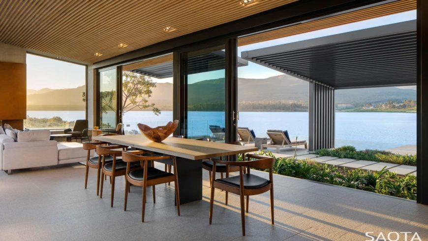 Airy dining room boasts concrete tiled flooring and glass sliders that open to the patio with a breathtaking lake view. It has wooden round back chairs and a rectangular dining table topped with a decorative bowl.
