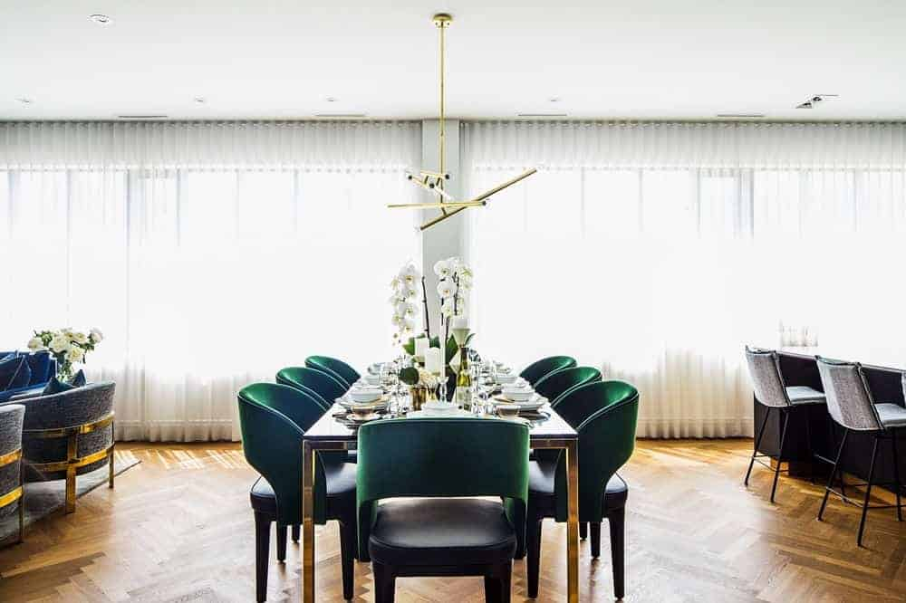 This dining room features a brass chandelier and metal dining table surrounded by green round back chairs. It has herringbone wood flooring and full height windows covered with white sheer curtains.
