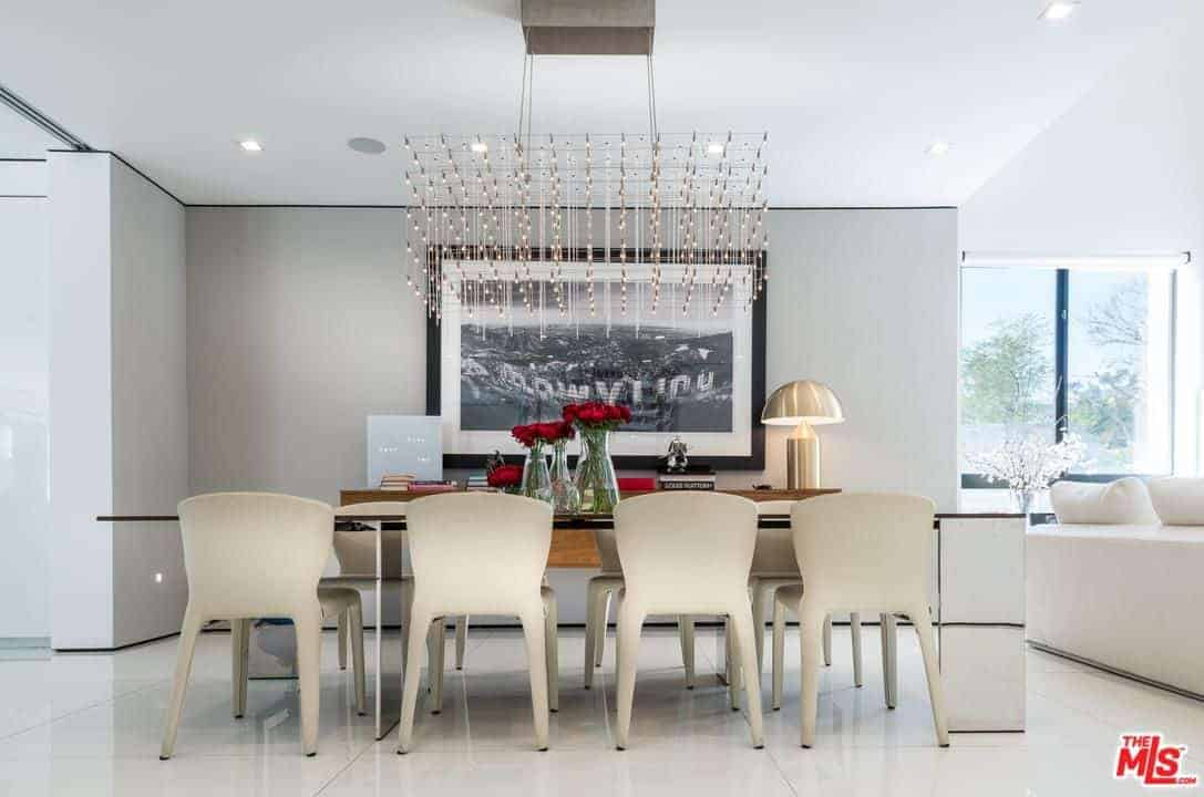 A chrome lampshade sits on a wooden buffet table in this dining area with a black framed wall art and a unique chandelier that hung over the modern dining set.