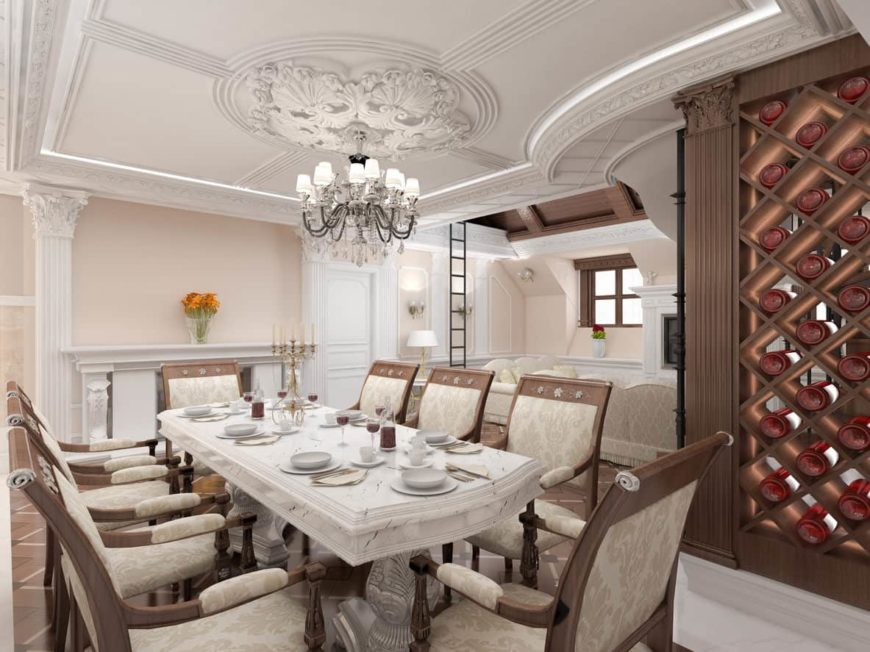 The luxury dining room offers a fireplace and a built-in wine rack arranged in a crisscross pattern. It includes a glam chandelier and a marble dining table surrounded with floral upholstered chairs.