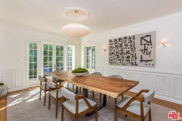 This dining room boasts gray cushioned chairs and a wooden dining table lighted by a round pendant light. It is designed with white wainscoting and a canvas flanked by wall sconces.