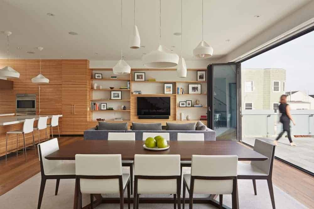 Various styled pendant lights hang over the smooth wooden dining table in this open dining room with sleek white chairs and a beige area rug that lays on the wood plank flooring.