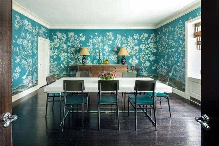A double door opens to this charming dining room clad in blue floral wallpaper. It has a dining set for eight and a wooden console table topped with black lampshades and translucent jars.