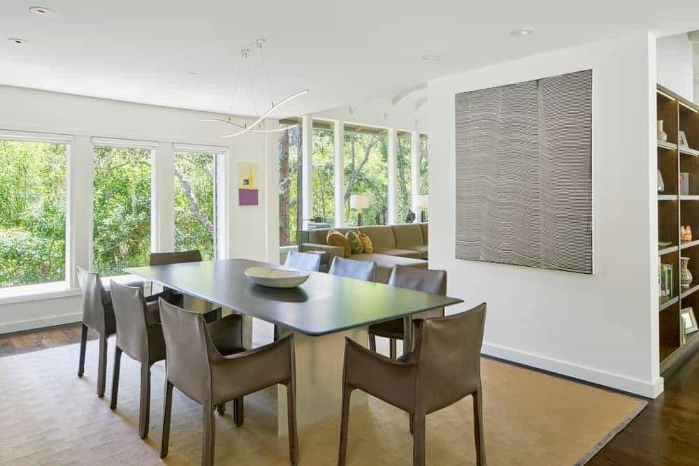 A white decorative bowl sits on a rectangular dining table in this fresh dining room with modern pendant lights and stylish brown armchairs that sit on a beige area rug.