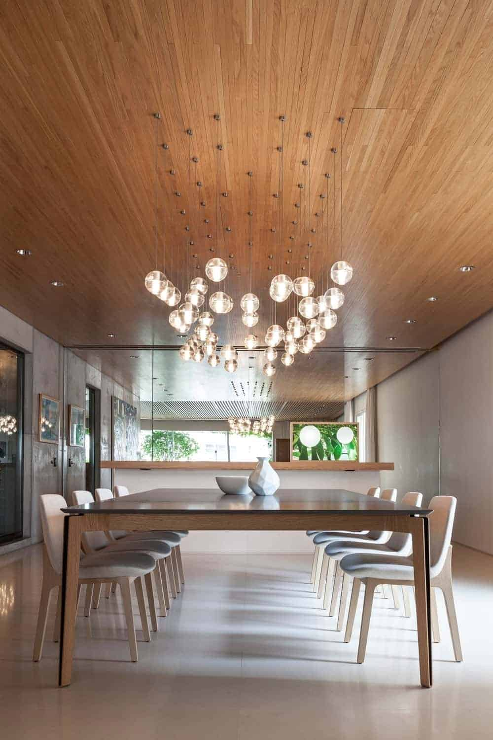 This dining room features a mirrored wall and sleek white chairs that sit at a wooden dining table topped with modern bowl and vase. It is illuminated by glass globe pendants and recessed lights mounted on the wood paneled ceiling.