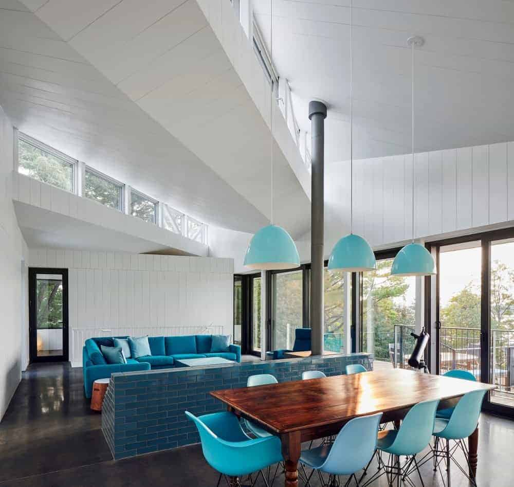 Contemporary dining area situated behind the living space showcases a dark wood dining table and blue modern chairs complementing with the dome pendant lights that hung from the shiplap ceiling.