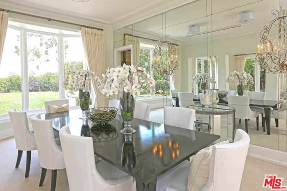 A black dining table adds a striking contrast in this white dining room offering wingback chairs and three-panel window framing the lush greenery. It is lighted by a pair of drum flush lights and ornate chandeliers reflected in the mirrored wall.