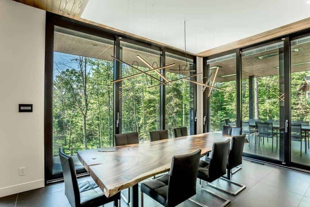 Modern pendant lights hang over the stump dining table surrounded by black leather chairs in this dining room with tiled flooring and full height windows framed in black aluminum.