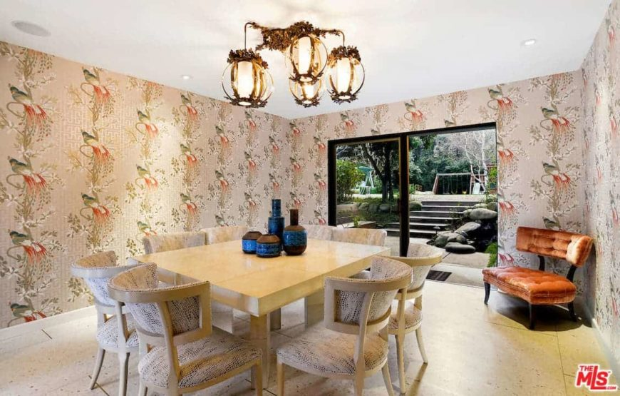 Clad in woodland bird wallpaper, this charming dining room offers wooden dining set for eight lighted by gorgeous glass pendants along with a tufted seat next to the glass slider that opens to a concrete staircase leading to the playground.