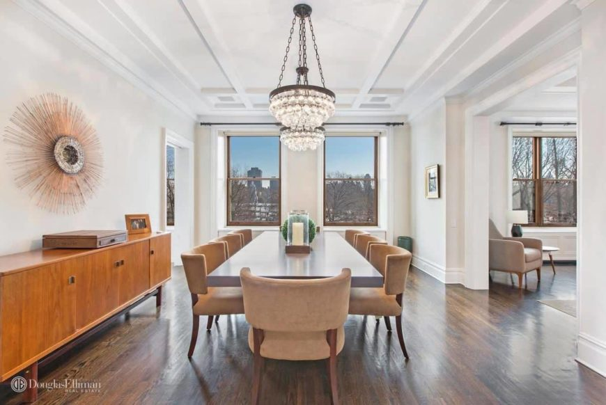 White dining room designed with crystal chandeliers and a sunburst decor mounted above the wooden console table. It has beige velvet chairs and a rectangular dining table that sits on the hardwood flooring.