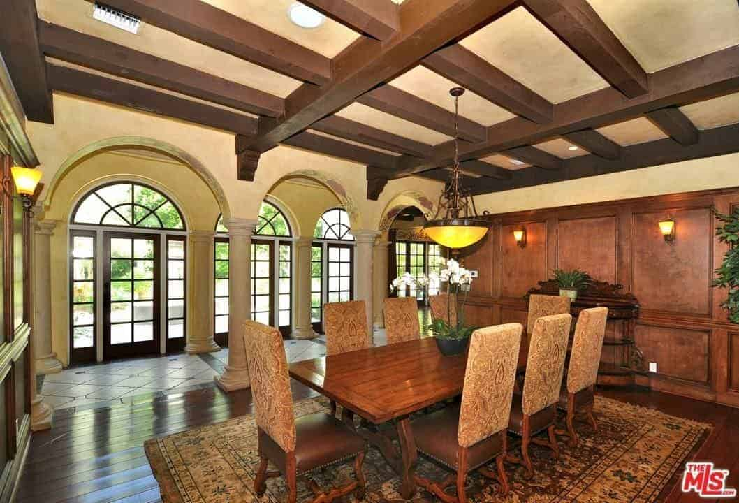Spanish style dining room with open archways and stylish wood beam ceiling mounted with recessed lights and a vintage pendant. It includes upholstered chairs and a rectangular dining table complementing with wood paneled walls and wood plank flooring topped by a classic area rug.