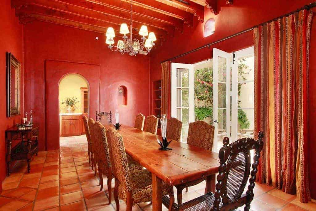 Red dining room with terracotta flooring and French door dressed in gorgeous striped draperies. It includes a vintage chandelier and a wood plank dining table paired with upholstered and wooden chairs.