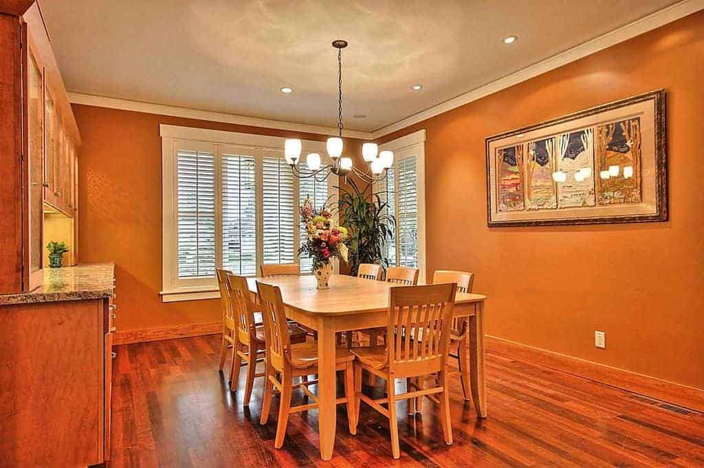 Warm dining room offers wooden dining set for eight and a rectangular artwork mounted on the orange wall. It includes a wrought iron chandelier and glazed windows covered with white shutters.